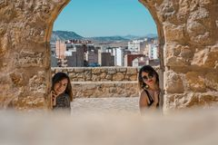 Women embrace and laugh while sitting on the castle stone. Two happy smiling young people friends outdoor. Two women on the castle stone royalty free stock image