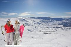 Two happy snowboarders in snow covered mountains Royalty Free Stock Photos
