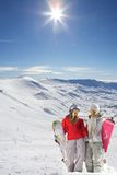 Two happy snowboarders in snow covered mountains Stock Photo