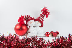 Two happy snowmen. With red hats, four red baubles and red garlands Royalty Free Stock Photo
