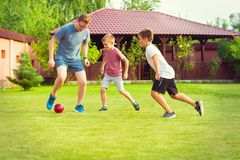 Two happy sons playing football with their father in garden near royalty free stock photography