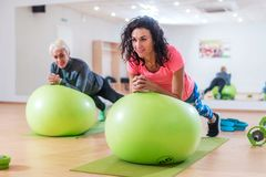 Two happy sportswomen exercising with a Swiss ball doing plank exercise in gym.  stock photos