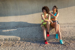 Two happy sporty women in sportswear sitting together Royalty Free Stock Images