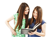 Two happy student girls reading the book. Portrait of two happy student girls reading the book. All on white background Royalty Free Stock Image