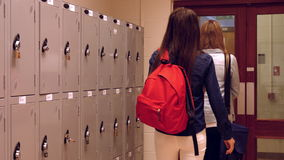 Two happy students chatting to each other. While opening lockers stock video