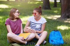 Two happy students friends laughing together in park with green background, sit in lotus position, wears casual clothes and stock photos