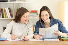 Two happy students reading a newspaper. Two happy students reading news in a newspaper at home Royalty Free Stock Photo