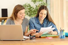 Happy students studying checking notes at home stock photo