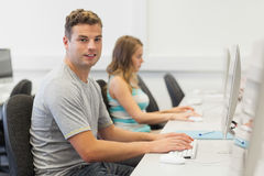 Two happy students working on computer individually Royalty Free Stock Image