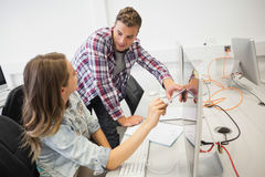 Two happy students working on computer pointing at it Royalty Free Stock Photography