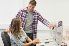 Two happy students working on computer Stock Photos