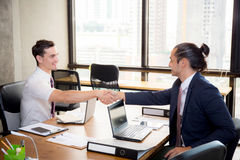 Two happy successful business partner shaking hands. Royalty Free Stock Images
