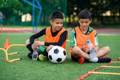 Free Two Happy Teen Boys In Football Uniforms Having A Rest On The Sport Field And Enjoying Fresh Water In The Break. Stock Photography - 194829462