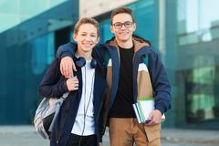 Two happy teenage friends standing together and looking in camera stock image