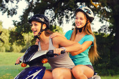 Two happy teenage girlfriends riding scooter Royalty Free Stock Photo