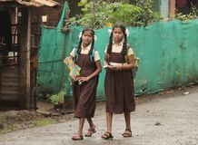 Two happy teenage girls go to school to get educated. Tribal girl students travel to school by walking a long distance in India village a sign of developing royalty free stock photo