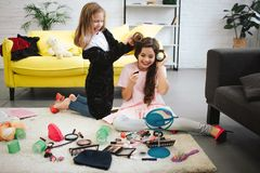 Two happy teenage girls having fun in room. They sit and stand on carpet. Blonde girl curling her friend`s hair stock images