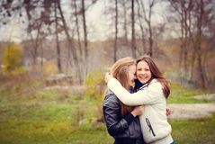 Two happy teenage girls hugging in the park in Royalty Free Stock Images