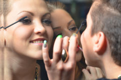 Two happy teenage girls putting on make up in front of mirror Royalty Free Stock Photo