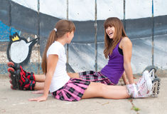 Two happy teenage girls in roller skates royalty free stock images