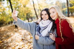 Two happy teenage girls taking a selfie on smartphone, outdoors in autumn in park royalty free stock image