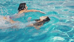 Two happy teenagers, a brother and sister, are swimming in a race in the pool. Slow motion. steadicam shot. 4k.  stock footage