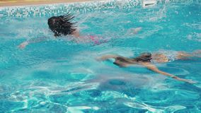 Two happy teenagers, a brother and sister, are swimming in a race in the pool. Slow motion. steadicam shot. 4k.  stock video