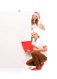 Two happy teenagers in Christmas hats pointing on a banner Royalty Free Stock Image