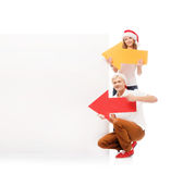 Two happy teenagers in Christmas hats pointing on a banner. Two happy teenagers in Christmas hats pointing on a large blank banner with arrows. The image is Royalty Free Stock Image