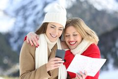 Two happy tourists searching on line in winter holidays Stock Photos