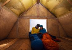 Two happy travelers are resting in the old mountain hut. Sitting in a sleeping bags next to a window and using a tablet pc. Awesome adventure in winter royalty free stock images