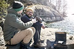 Two happy travelers are sitting on the rocky shore of the lake, chatting lively and drinking beer by the fire, on which food is. Prepared in a pot. Close-up stock photography