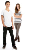 Two happy trendy teenagers. Full body studio portrait of two happy young trendy teenagers in smart casual clothes with the boy in the foreground and girl behind Royalty Free Stock Photo