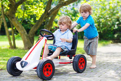 Two happy twin boys driving toy car royalty free stock photo