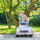 Two happy twin boys playing with toy car Stock Images
