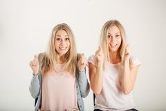 People, emotions and feelings. twin women having excited and winning looks. Two happy twin women having excited and winning looks, cheering, celebrating their Royalty Free Stock Photo