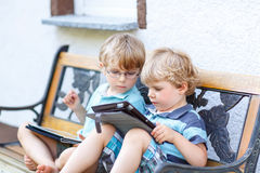 Two happy twins boys friends holding tablet pc, outdoors. Stock Photo