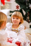 Two happy twins girl sitting near Christmas tree Stock Photo