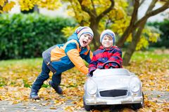 Two happy twins kids boys having fun and playing with big old toy car in autumn garden. Outdoors. Brother pushing car for child. Happiness, fun, leisure in stock photography