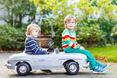 Two happy twins playing with big old toy car in summer garden, o Royalty Free Stock Photo