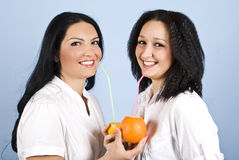 Two happy woman drink orange juice. Two beautiful and happy woman standing face to face and looking you.They drink fresh orange juice from  raw fruit orange and Royalty Free Stock Images