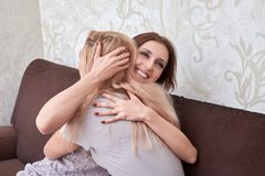 Two happy woman hug each another and sitting on sofa in living room at home. royalty free stock images