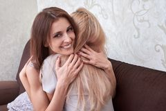 Two happy woman hug each another and sitting on sofa in living room at home. stock image