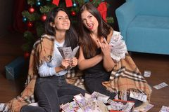 Two happy woman sit under a Christmas tree on the floor strewn with money stock image