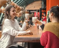 Two happy women are sitting in a cafe, drinking milkshakes. Two happy woman are sitting in a cafe, drinking milkshakes, telling each other funny stories, being royalty free stock photo