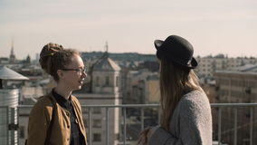 Two happy woman talking against the background of city panorama, roofs. Friends walking in downtown in sunny day. Stylish female enjoying the leisure time stock footage