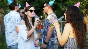 Two happy woman talking and drinking beer on summer party, men in the background, wearing holiday caps. Two happy woman talking and drinking beer from bottle on stock video footage