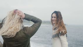 Two happy woman traveling together. Girl having fun on beach near troll toes in Iceland, raising up hands and hugging. Two happy woman traveling together. Girl stock video
