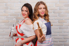 Two happy women in apron at kitchen. Royalty Free Stock Images