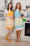 Two happy women in apron at kitchen. Stock Photo